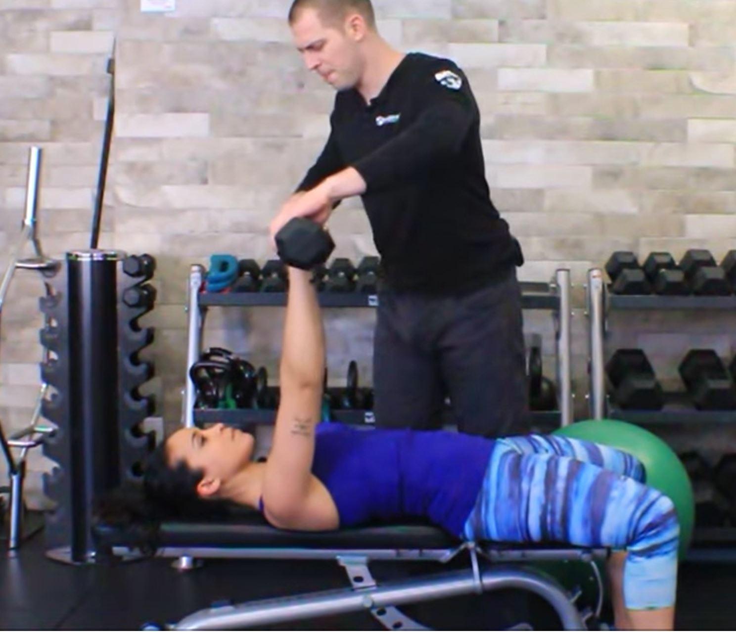 Dr. Brent Brookbush cues Melissa through multi-planer dumbbell press on bench
